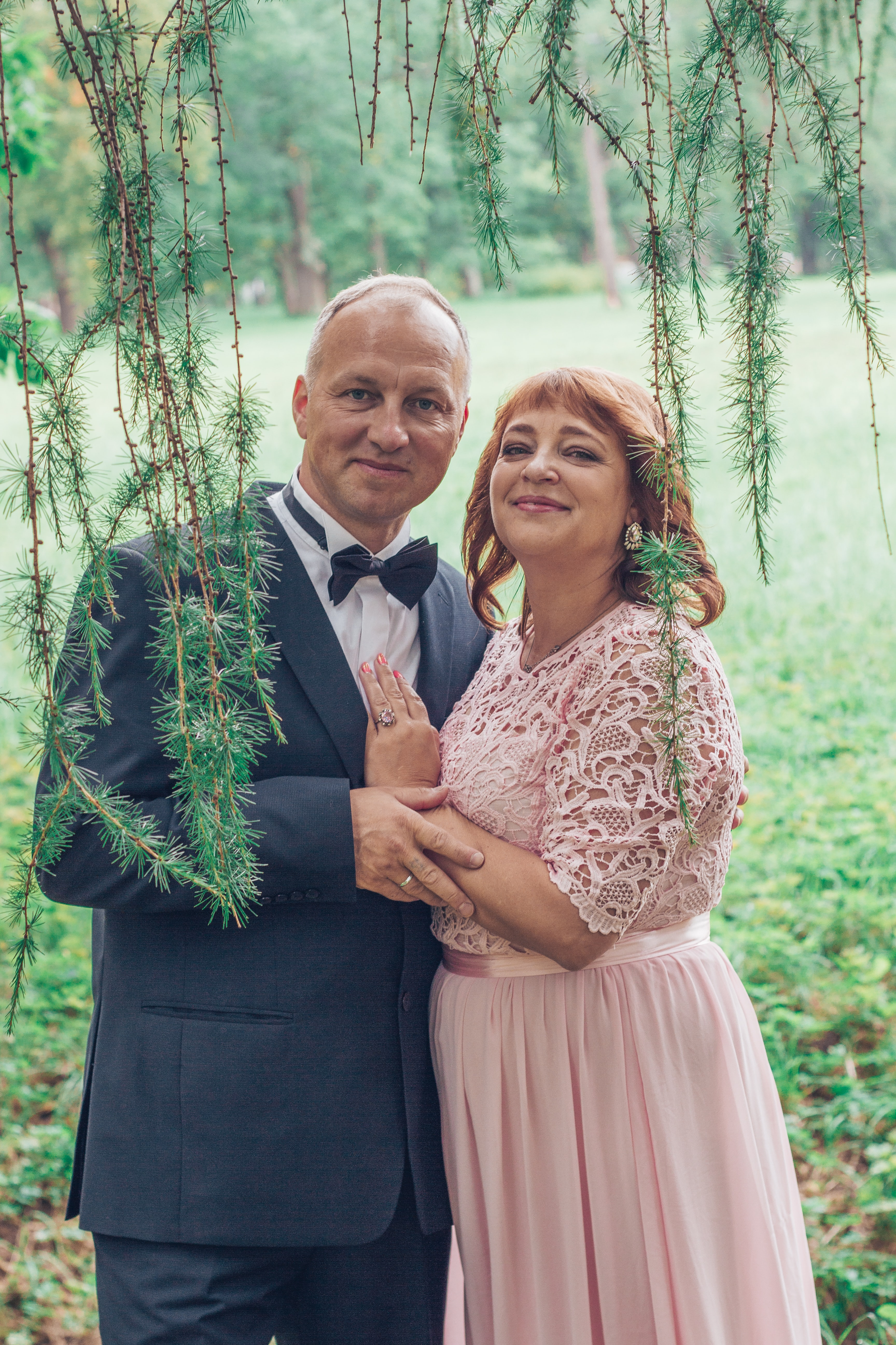 couple holding under the leafed tree