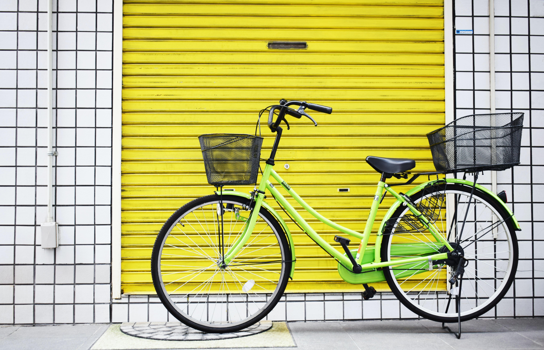 green cruiser bike near yellow gate