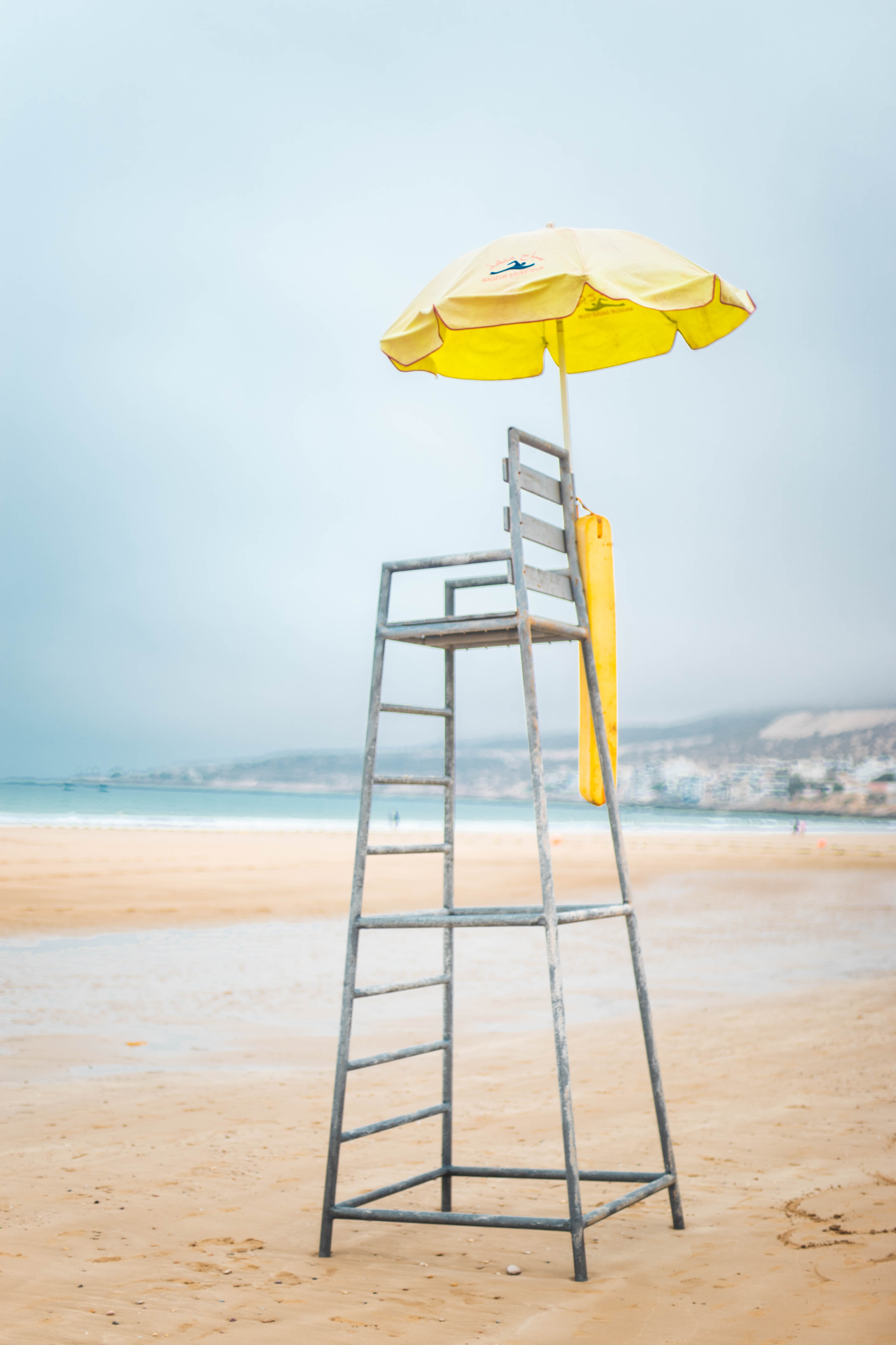 gray and brown lifeguard chair near body of water