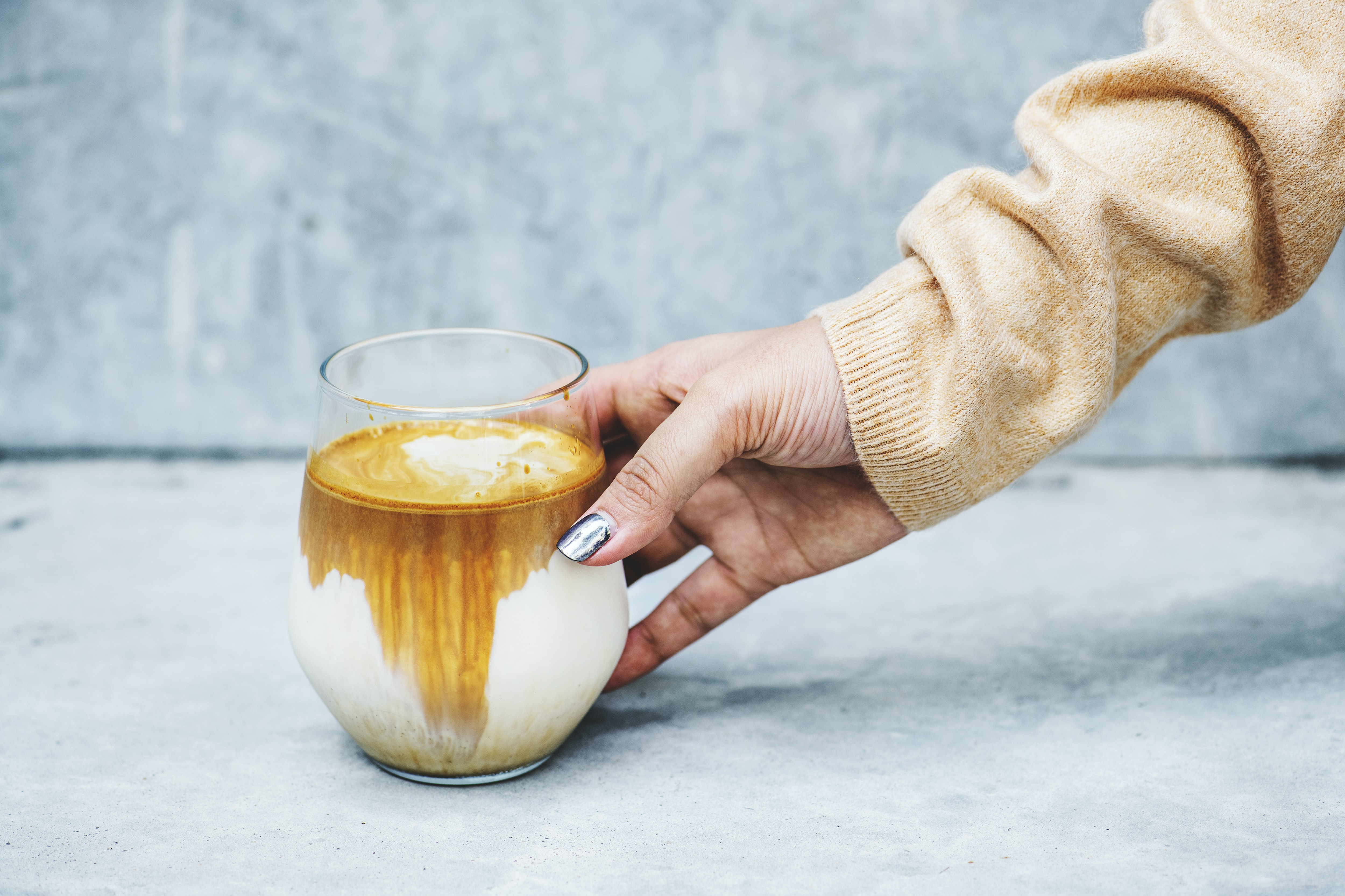 person holding cup filled with brown and white liquid