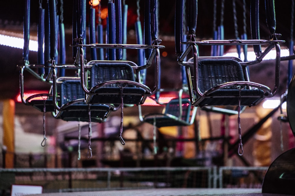 selective focus photography of gray hanging chairs
