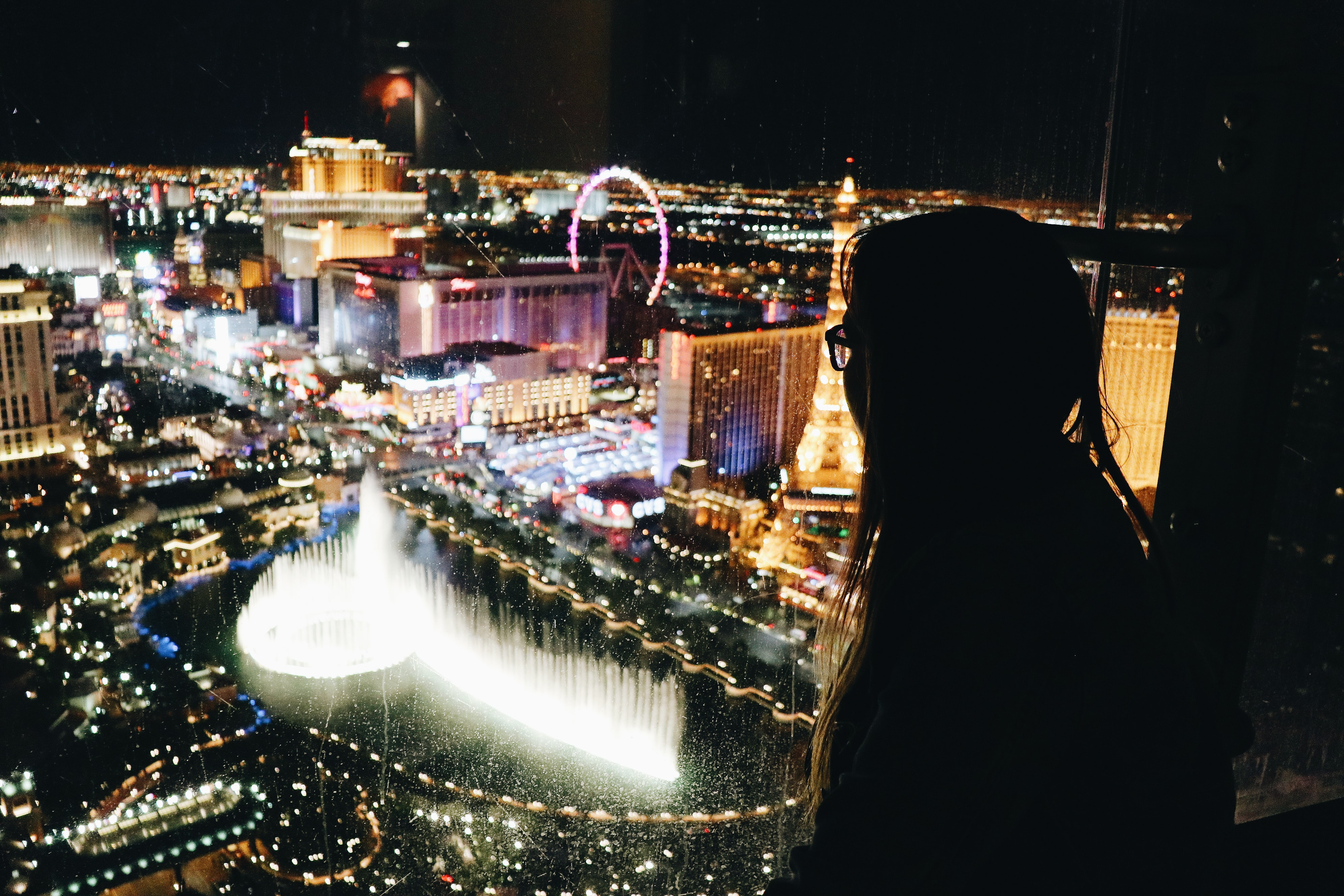 woman standing near edge of building watching at fountain in front of Las Vegas Paris building