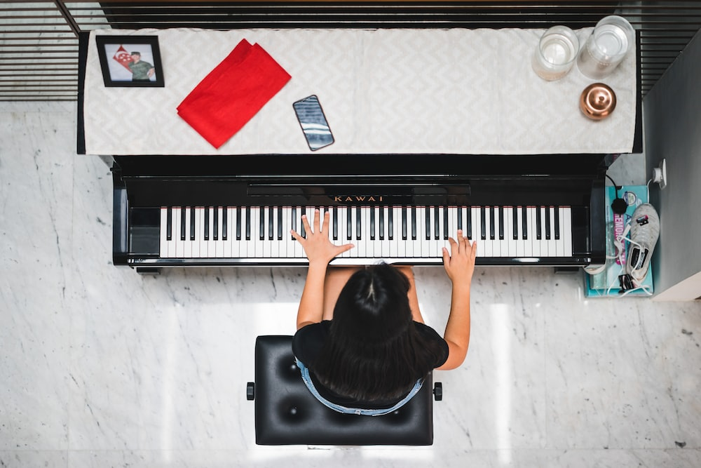 woman playing piano near white wall inside room