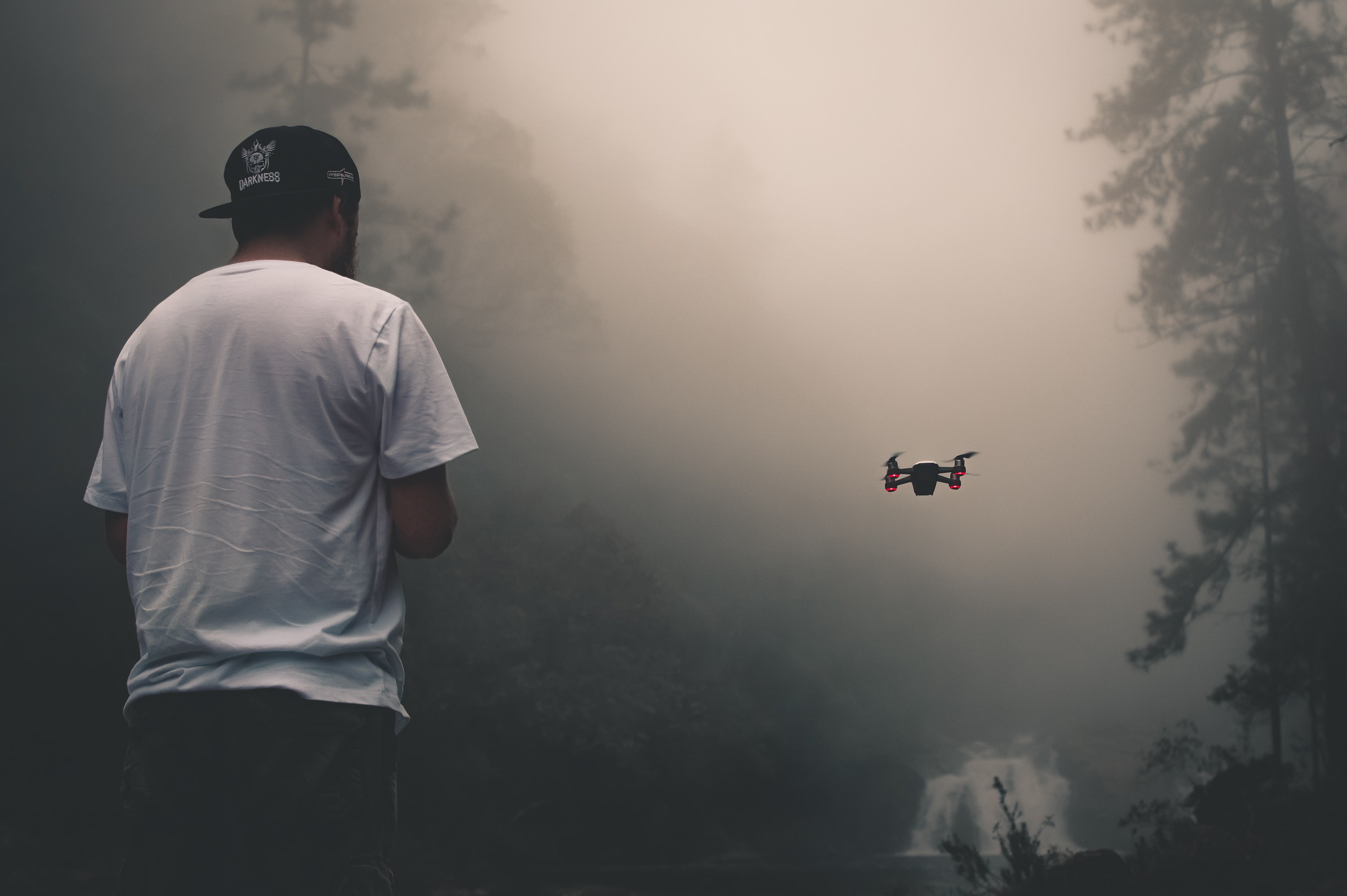person facing drone near tree during daytime