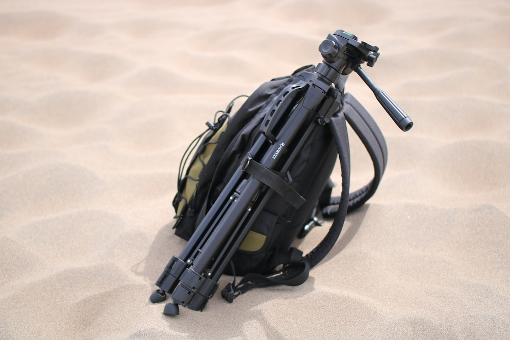 black tripod and yellow backpack on sand