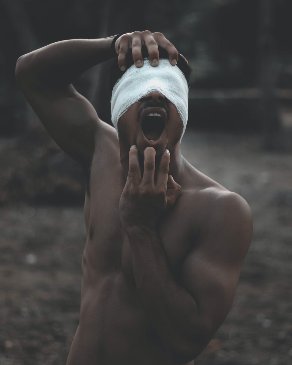 photo of topless man with bandage on his eyes