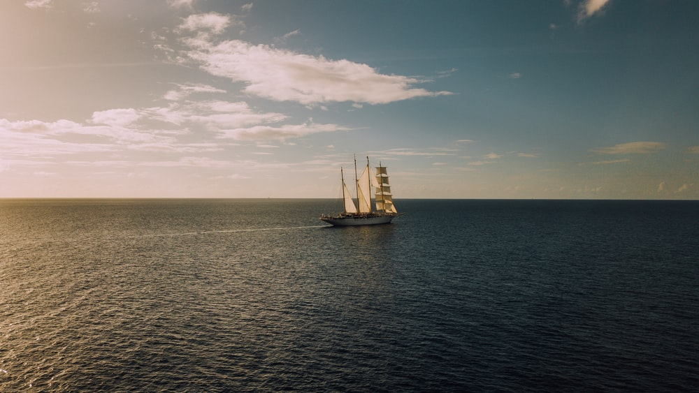 sailboat in middle of ocean under blue sky