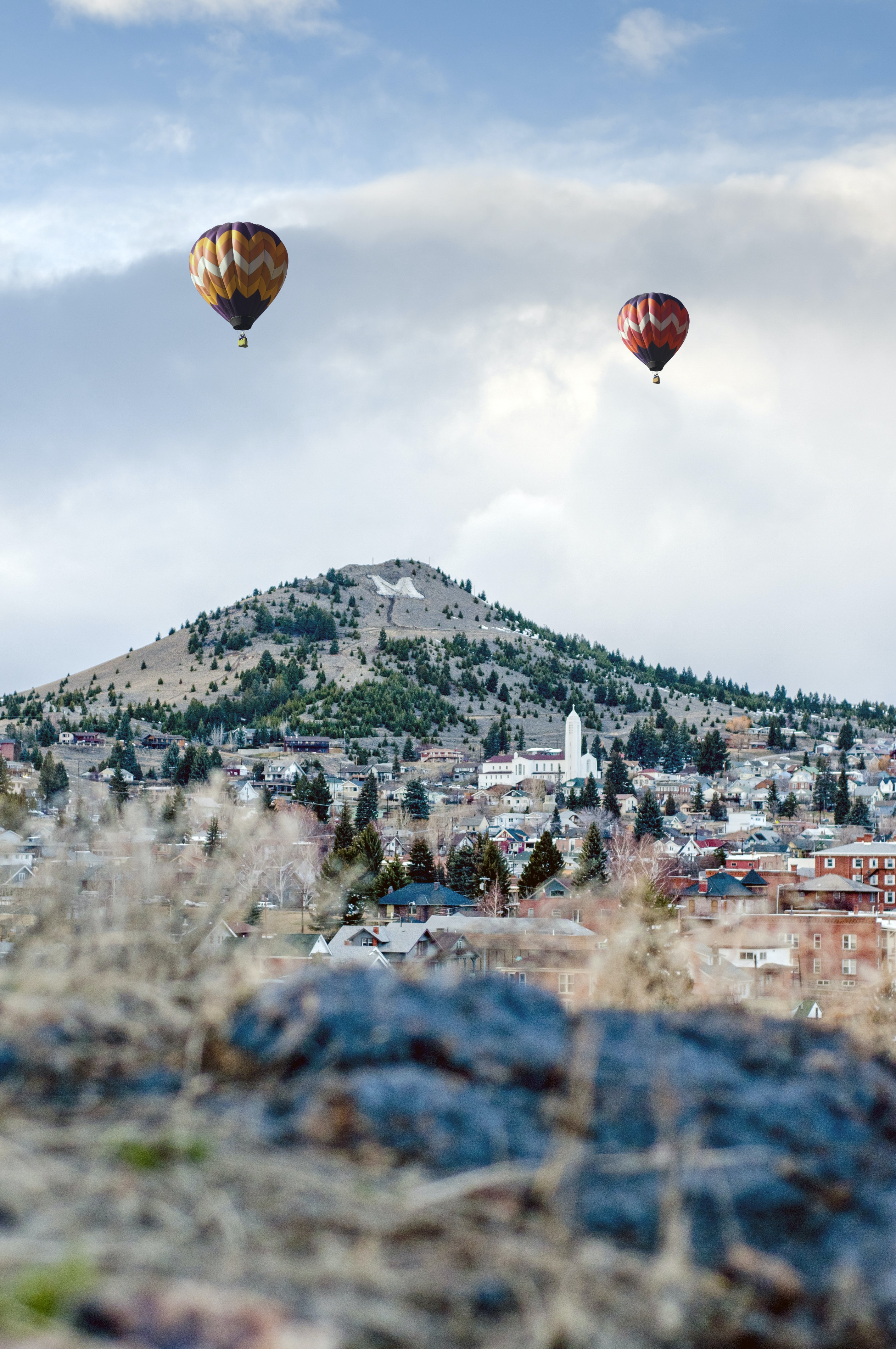 two assorted-color hot air balloons on air near mountain at daytime