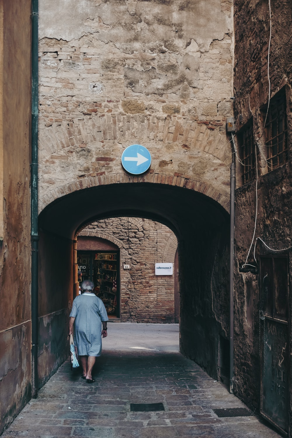 woman walking in gray and brown alley during daytime