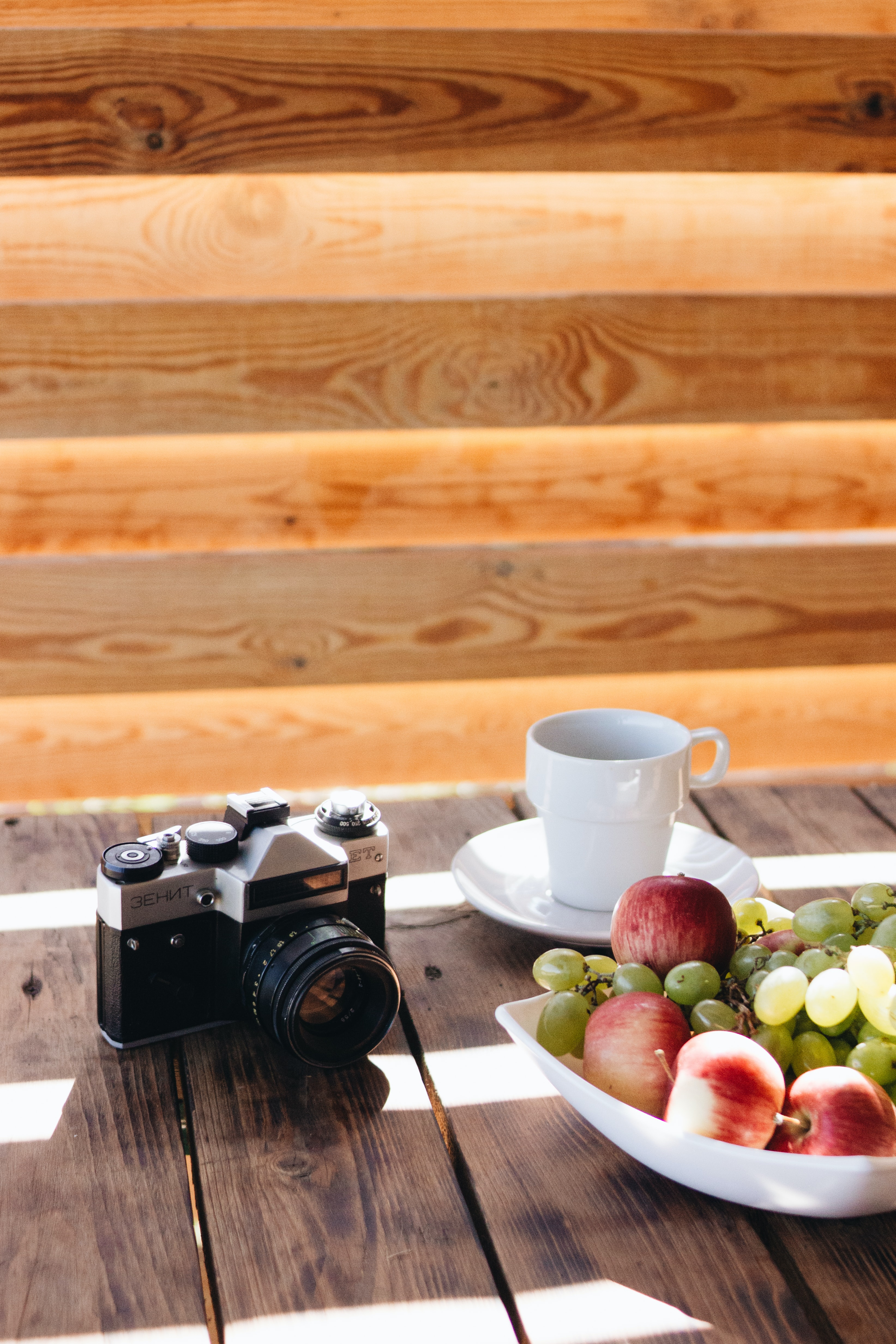 black and gray IMC camera beside white cup on saucer and fruits in bowl