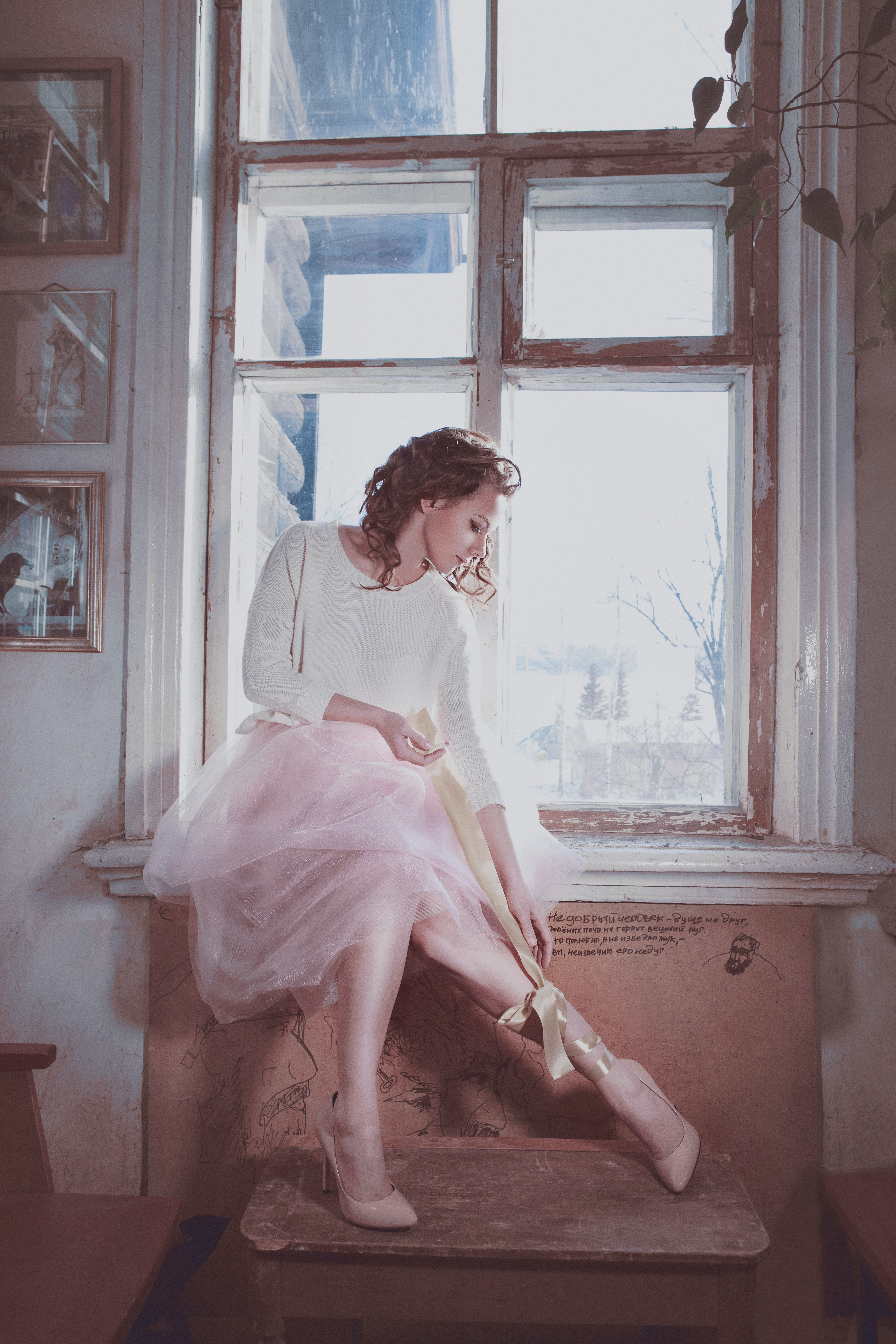 woman in white and pink dress sitting near window