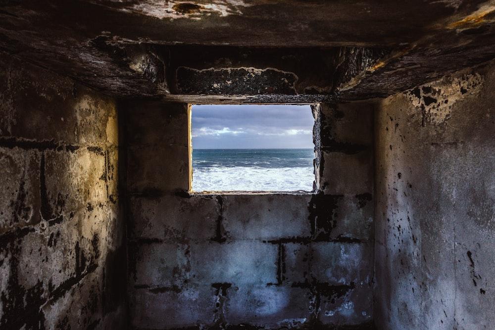 grey concrete window overlooking body of water