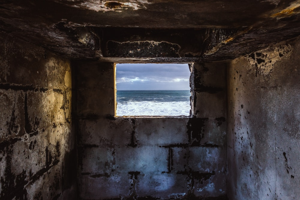 grey concrete window overlooking body of water