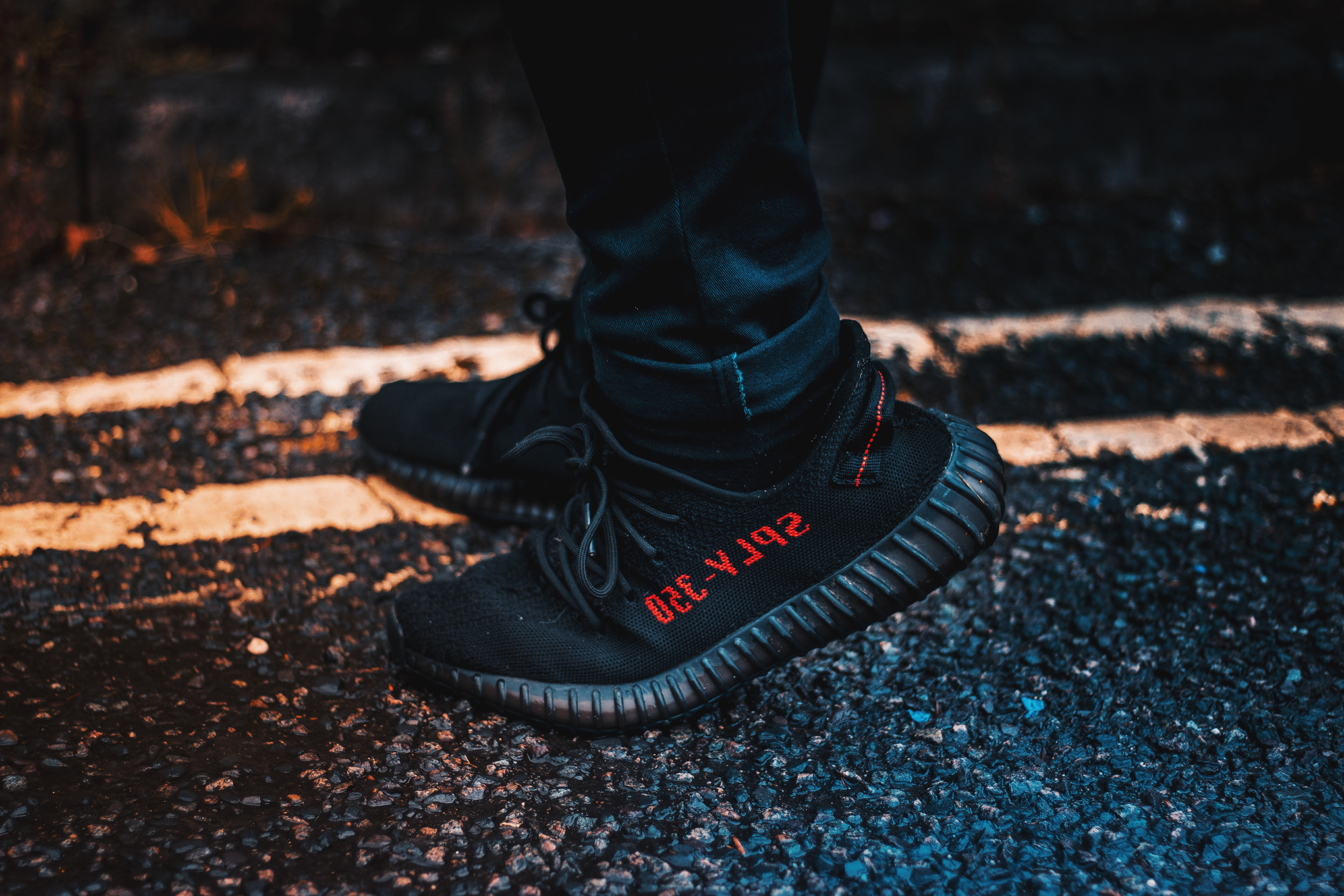 person wearing black adidas Yeezy Boost 350 V2 shoes