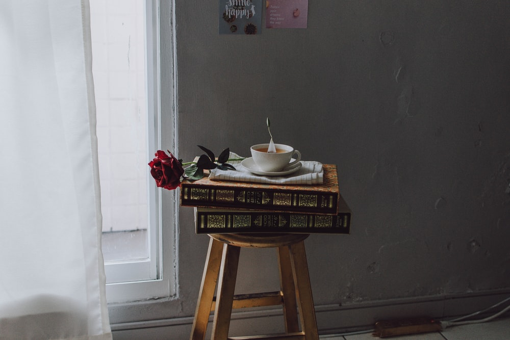 white ceramic teacup on saucer plate on books on stool near window at room