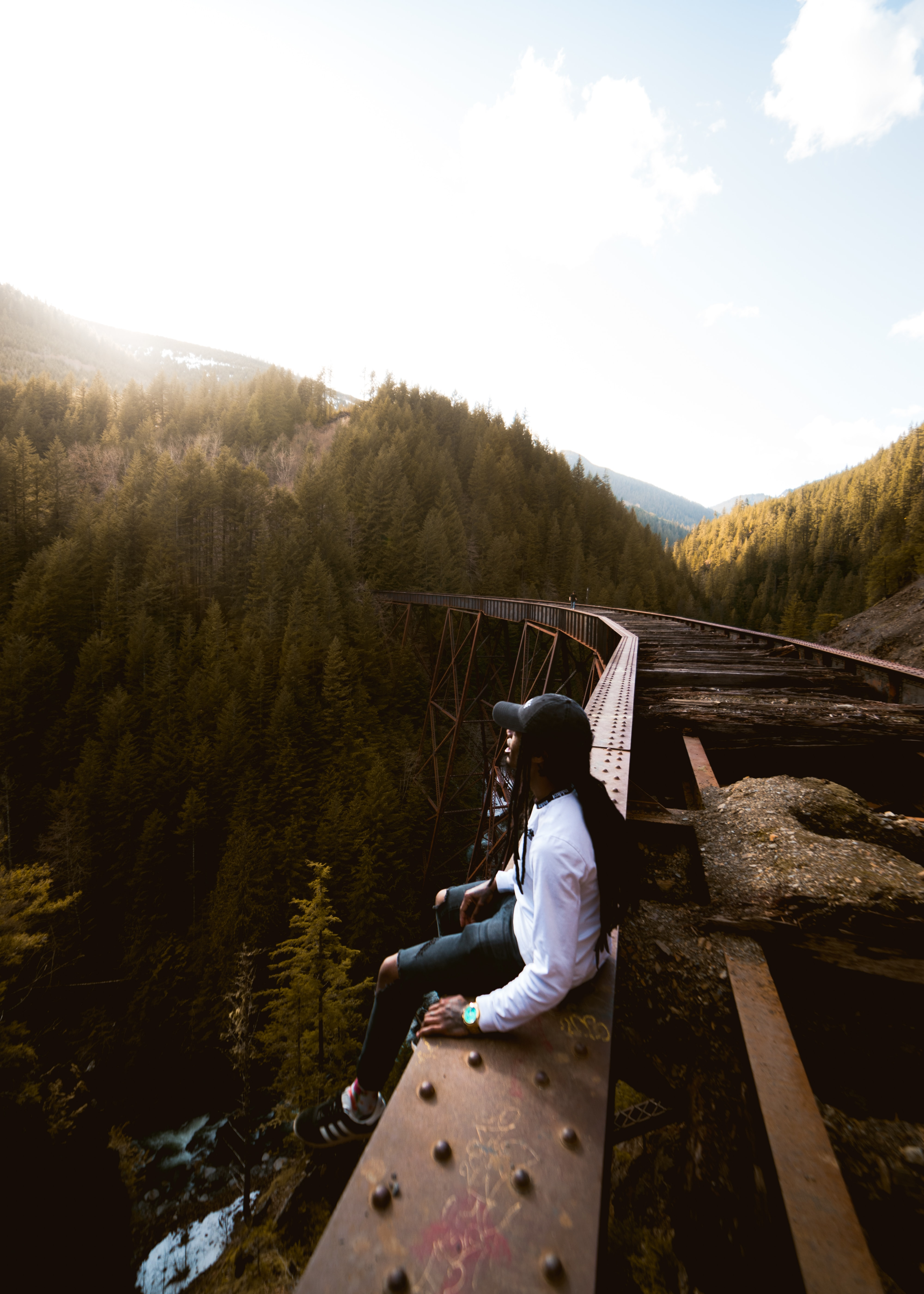 person sitting beside train rail and facing pine trees