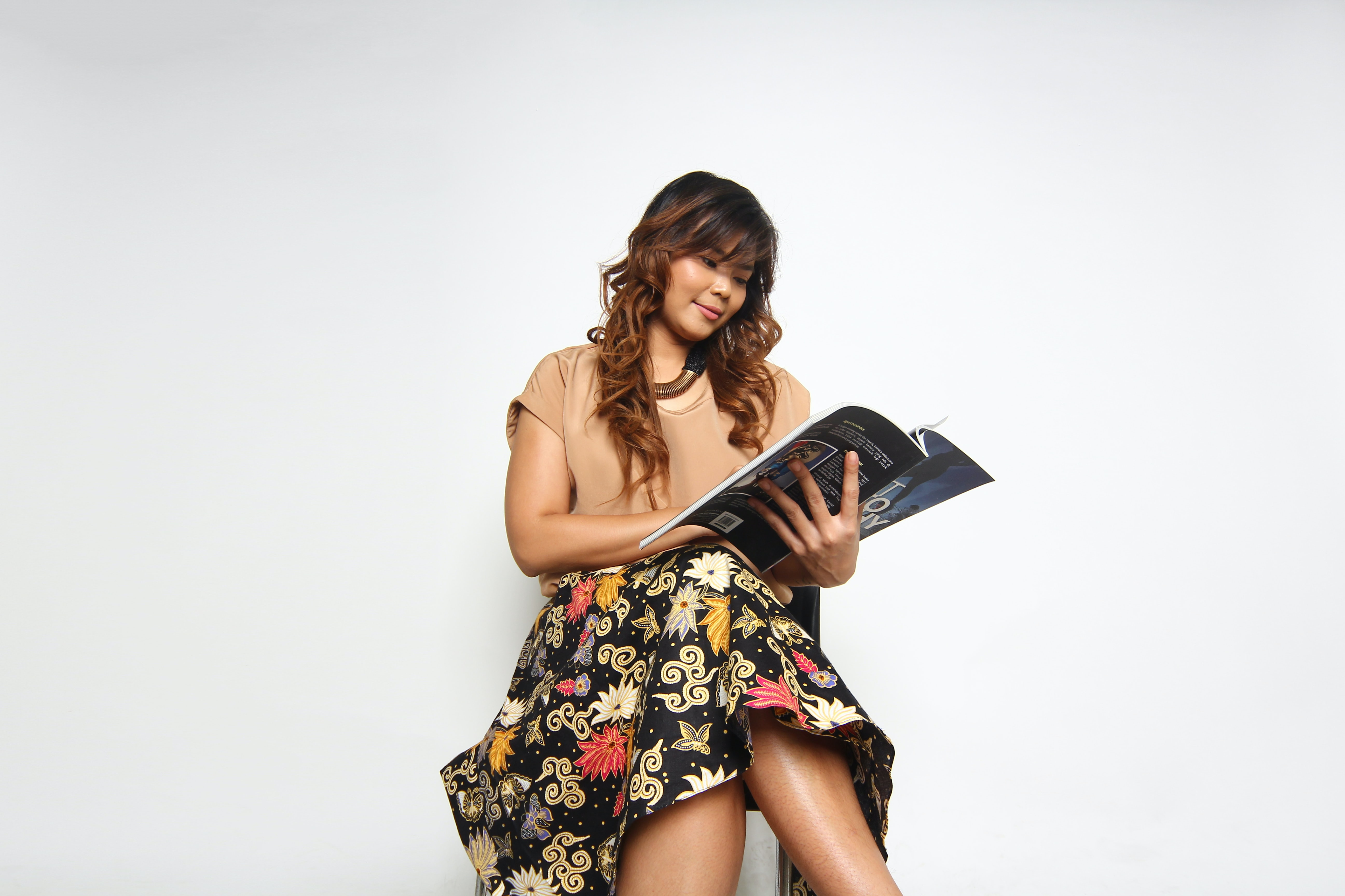 woman sitting on chair reading book