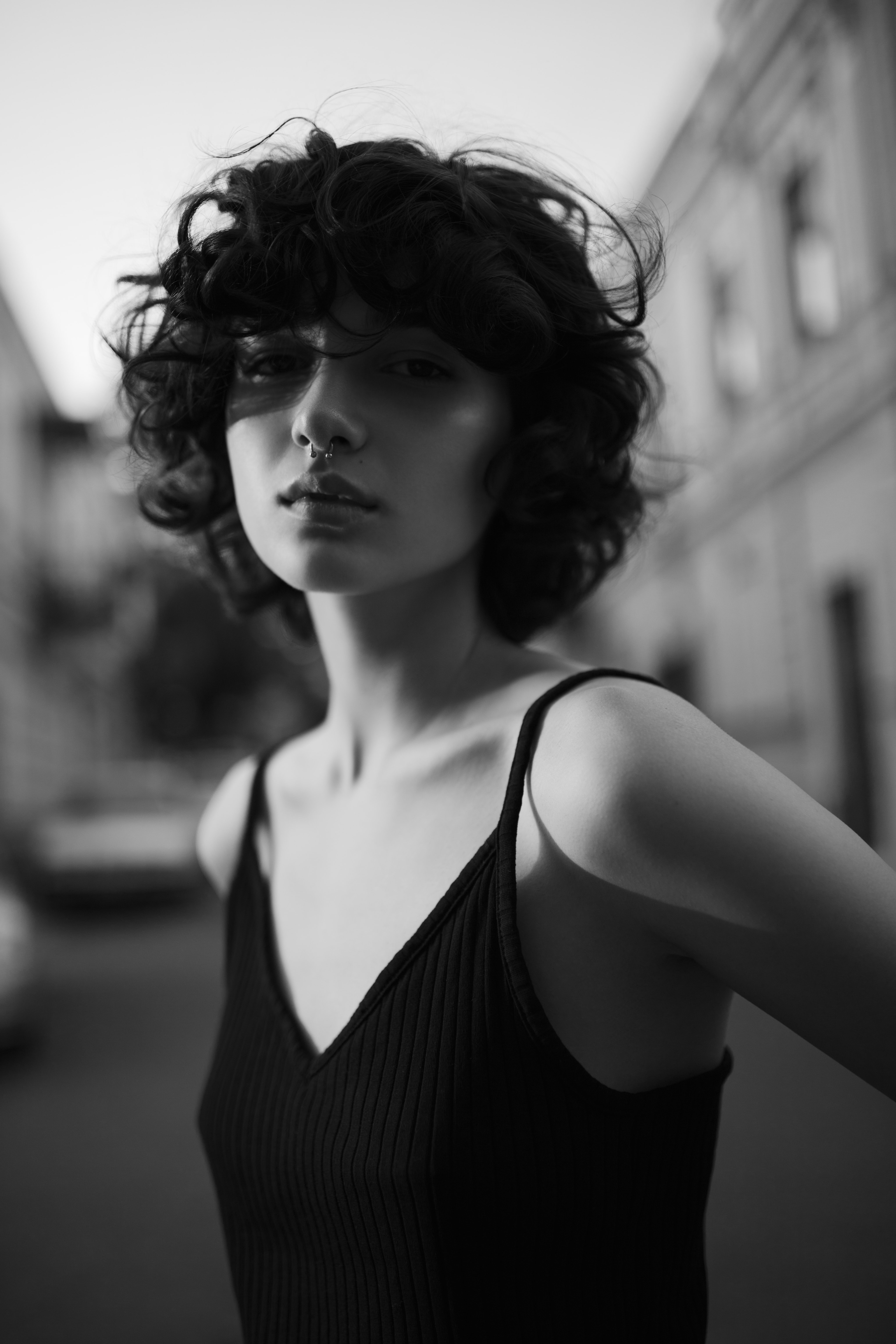 grayscale photo of woman wearing black spaghetti strap top