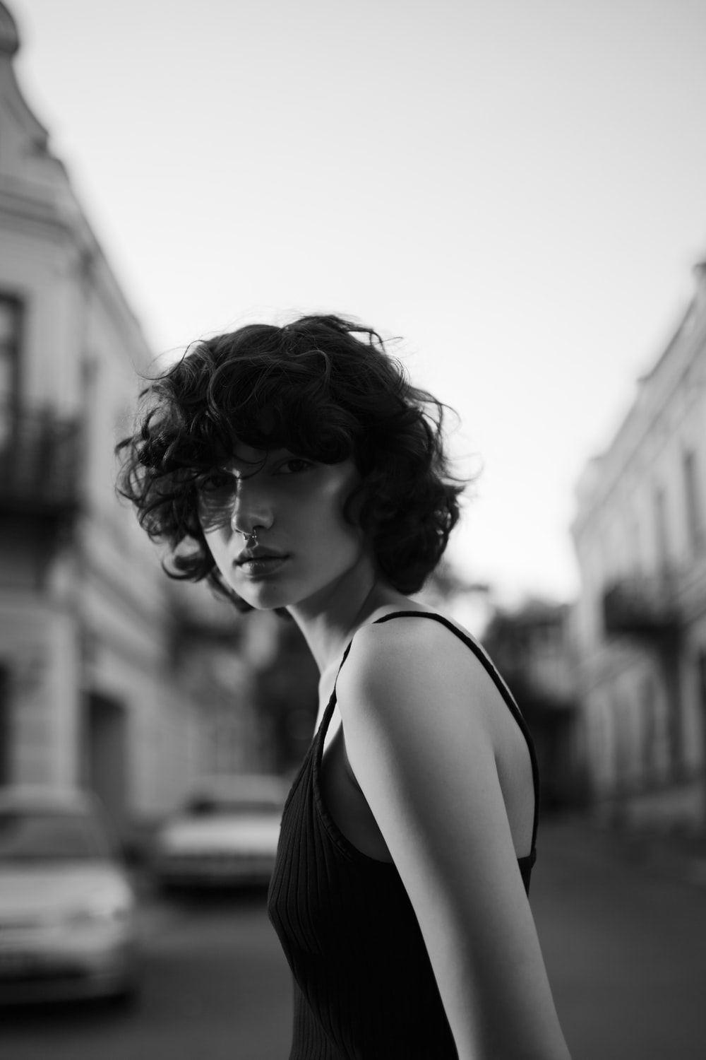 grayscale photography of woman in black spaghetti strap top in middle of road