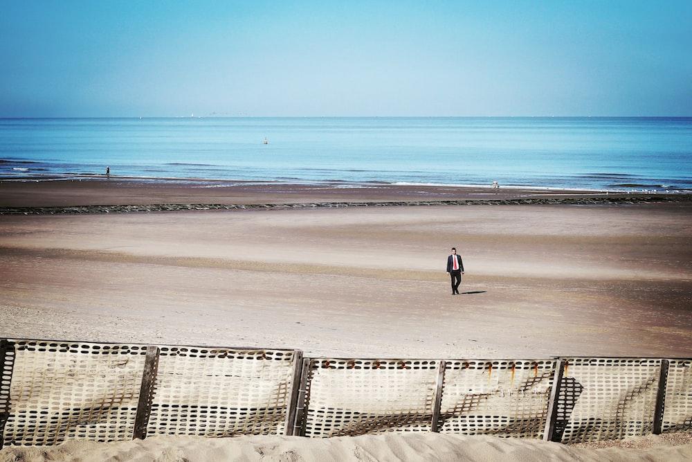 man walking at the coastline near white fences