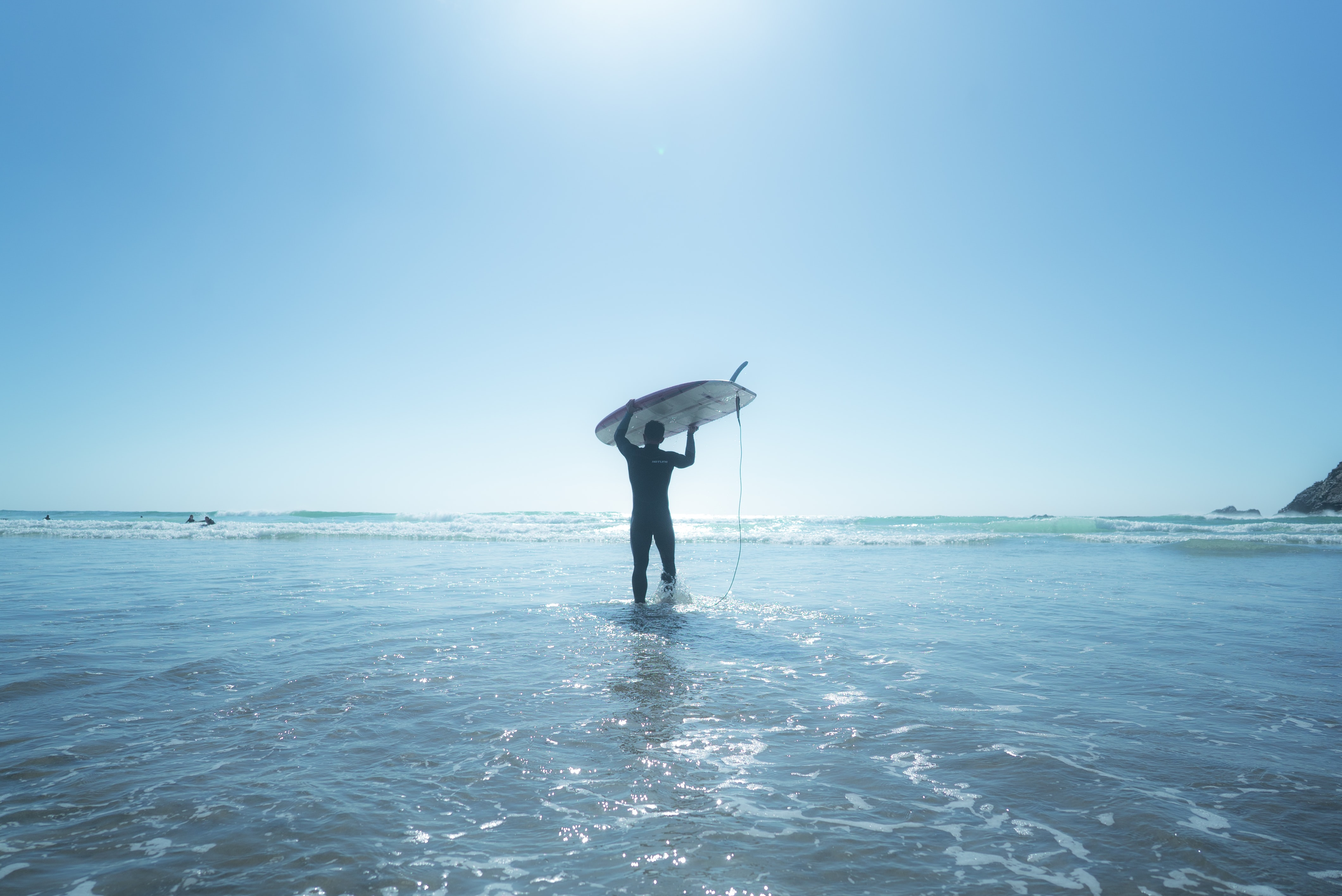man holds surfboard on water
