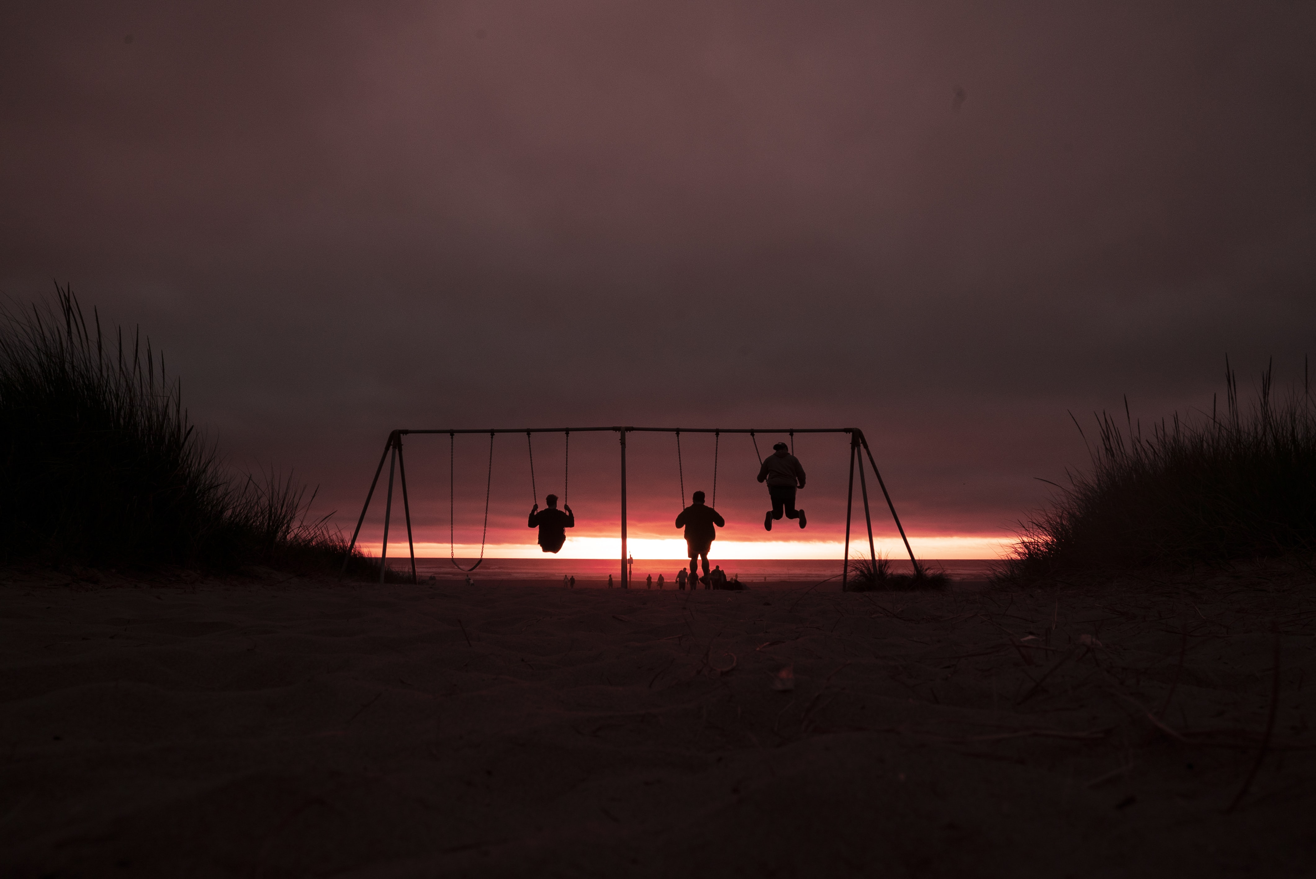 silhouette of three person swinging on outdoor swing