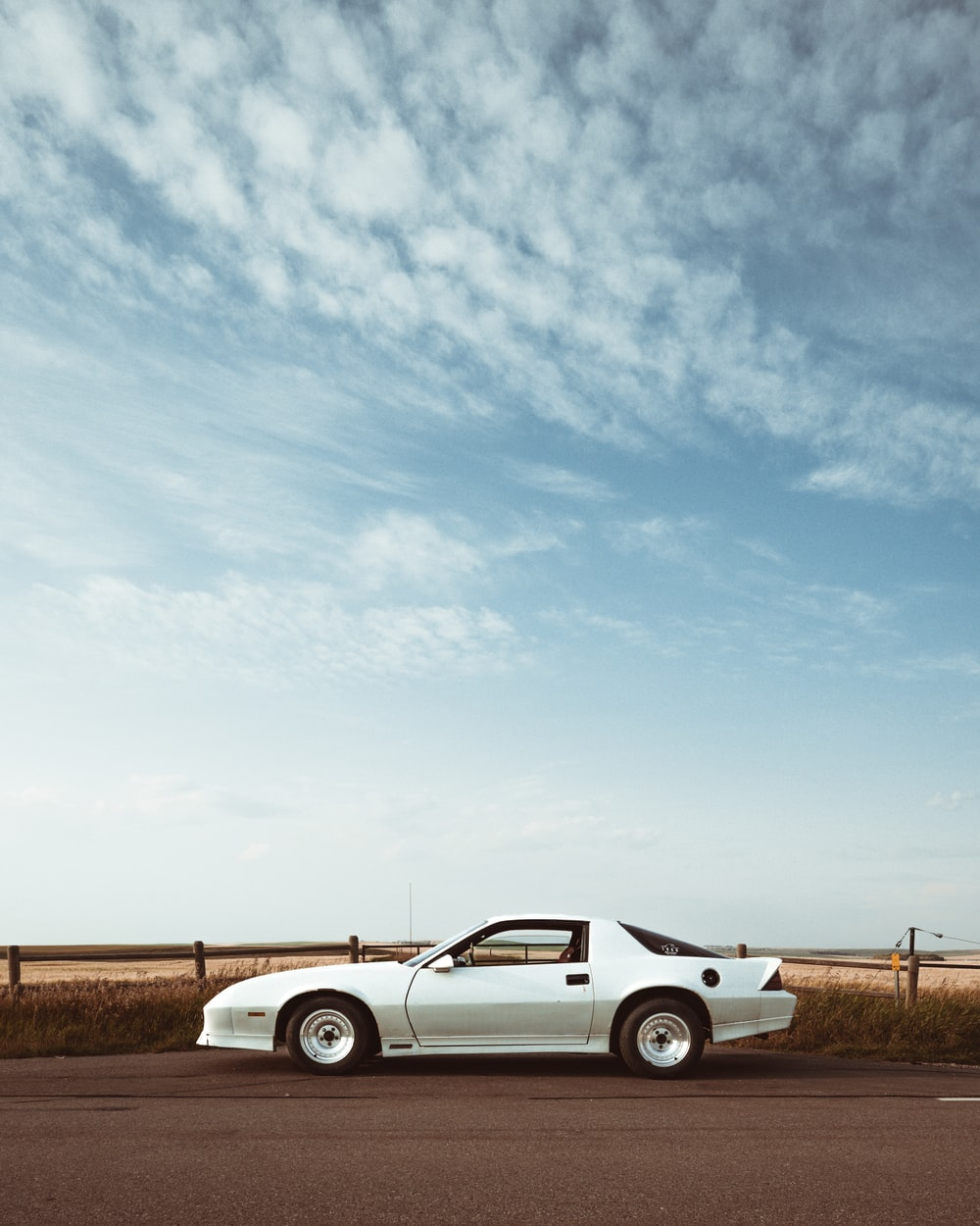 silver coupe under cloudy sky