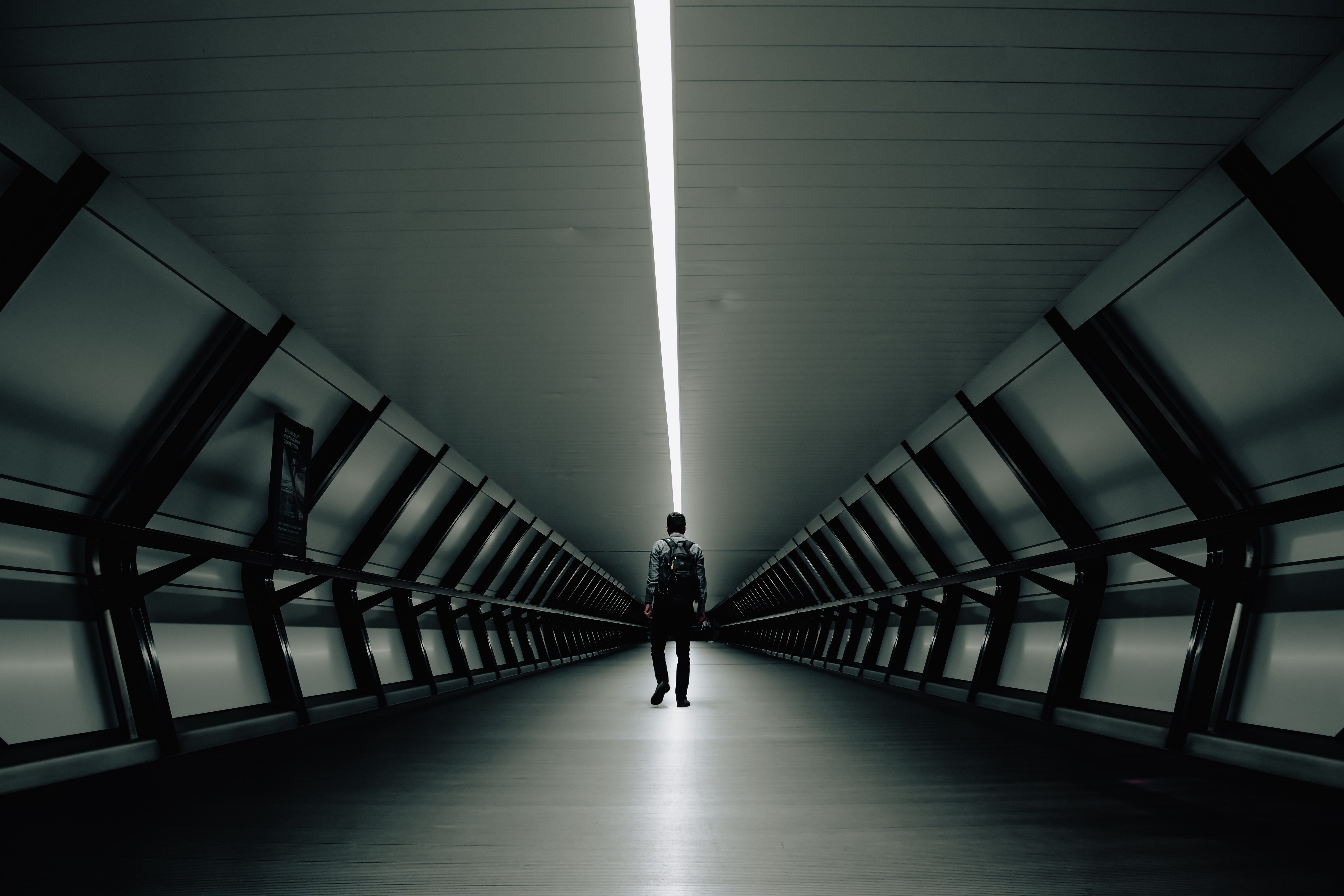 man walking inside tunnel
