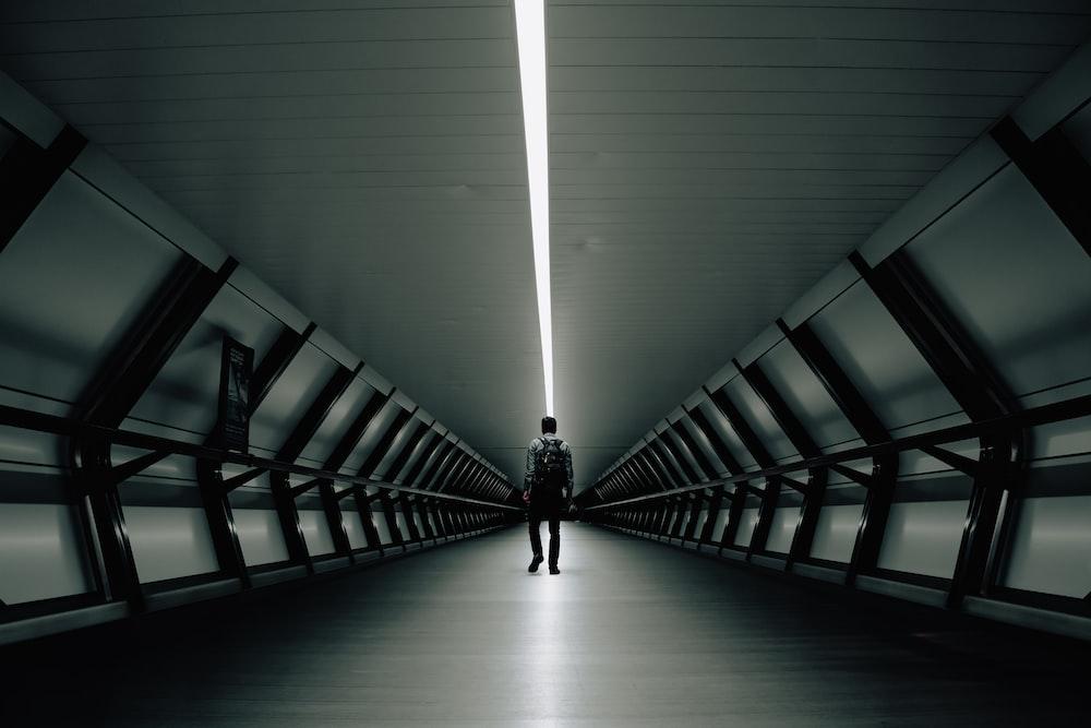 man walking inside tunnel