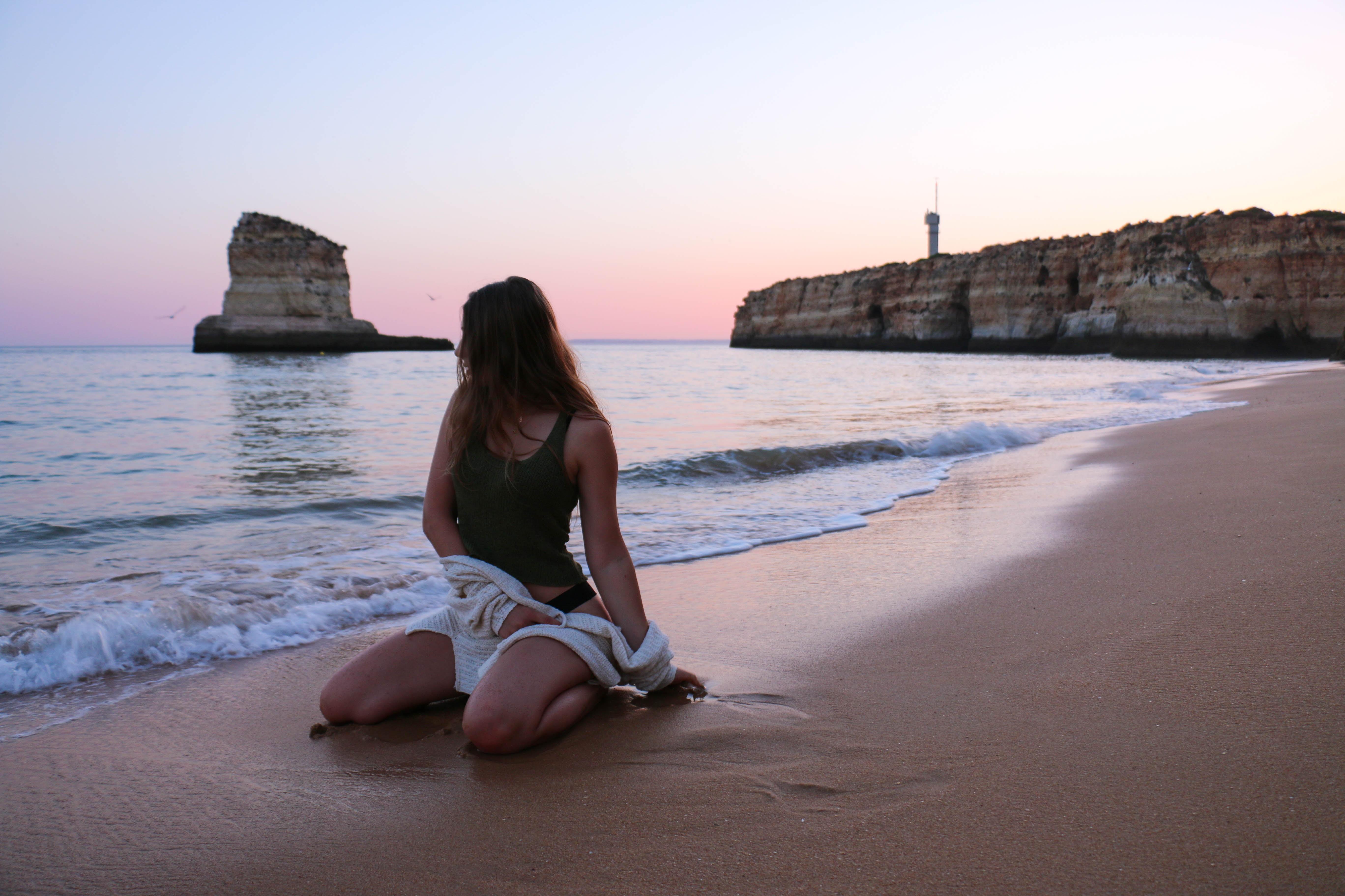 woman wearing black tank top sitting on gray sand near beach