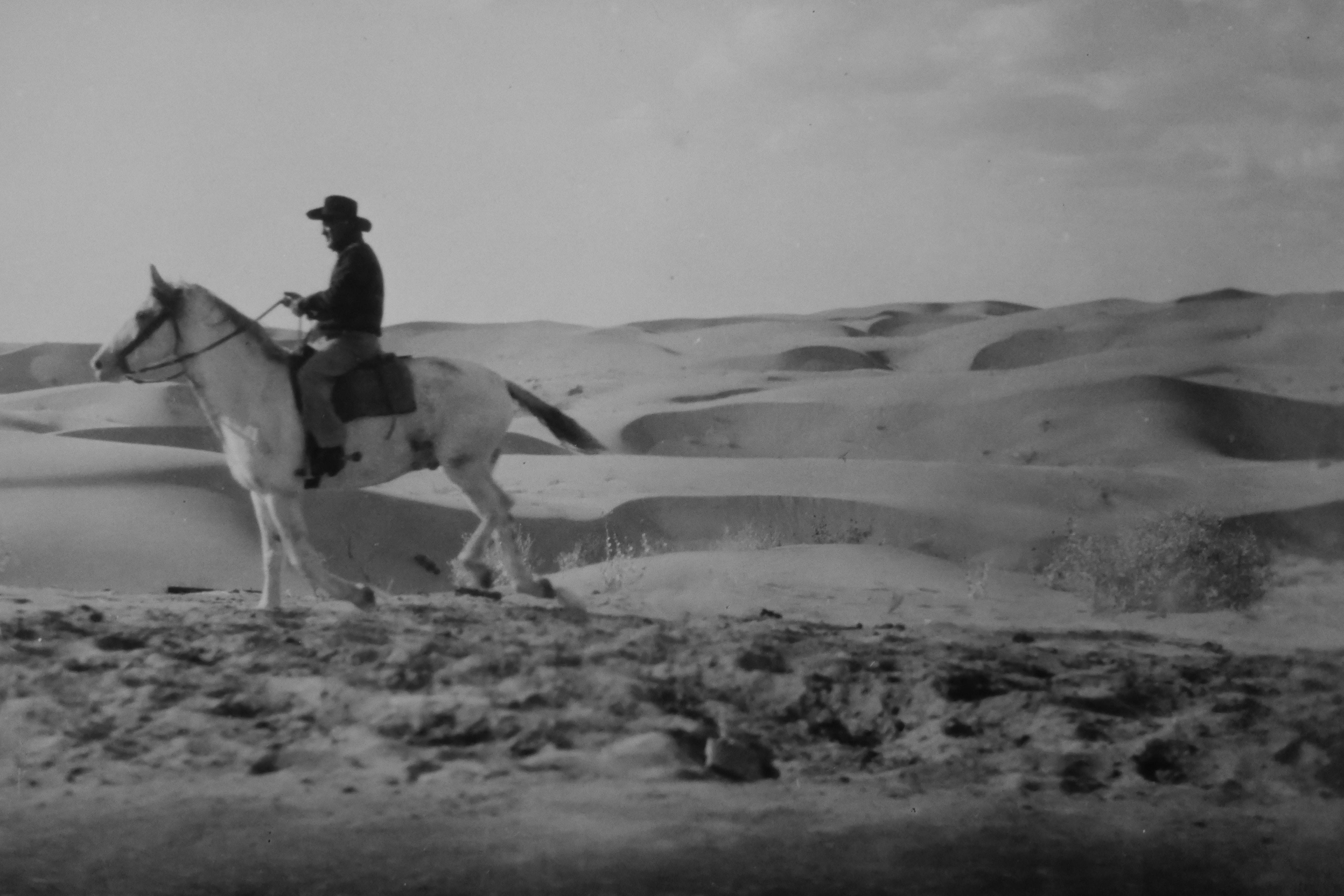 man riding horse on desert