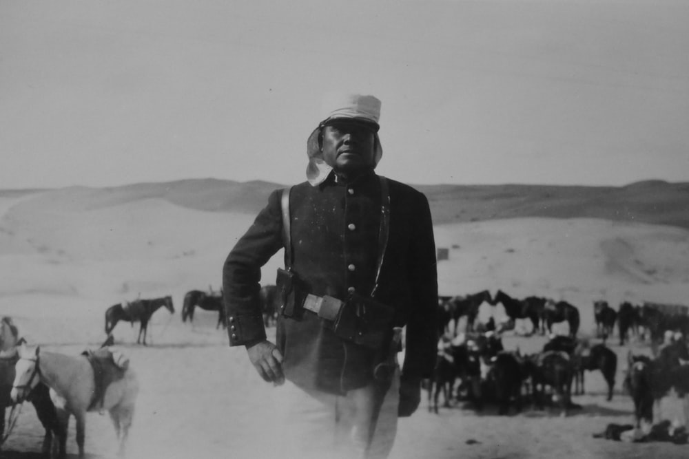grayscale photo of a soldier on desert with horse