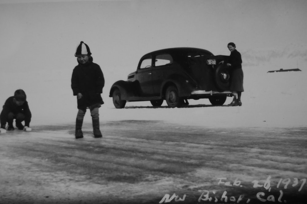 grayscale photo of two boys near vintage black car