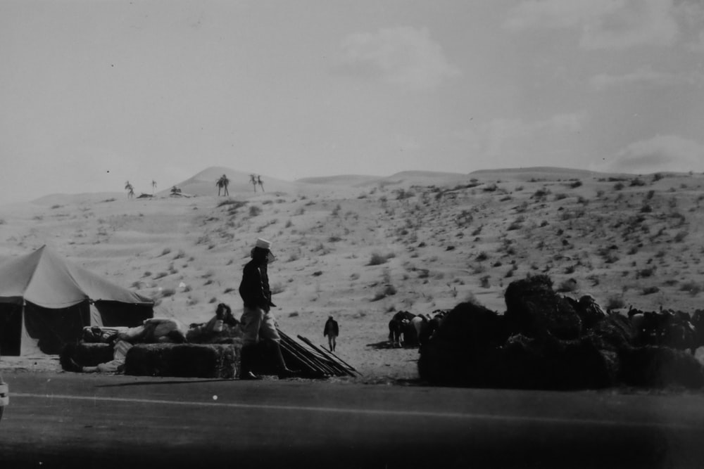 grayscale photography of man standing on vast valley