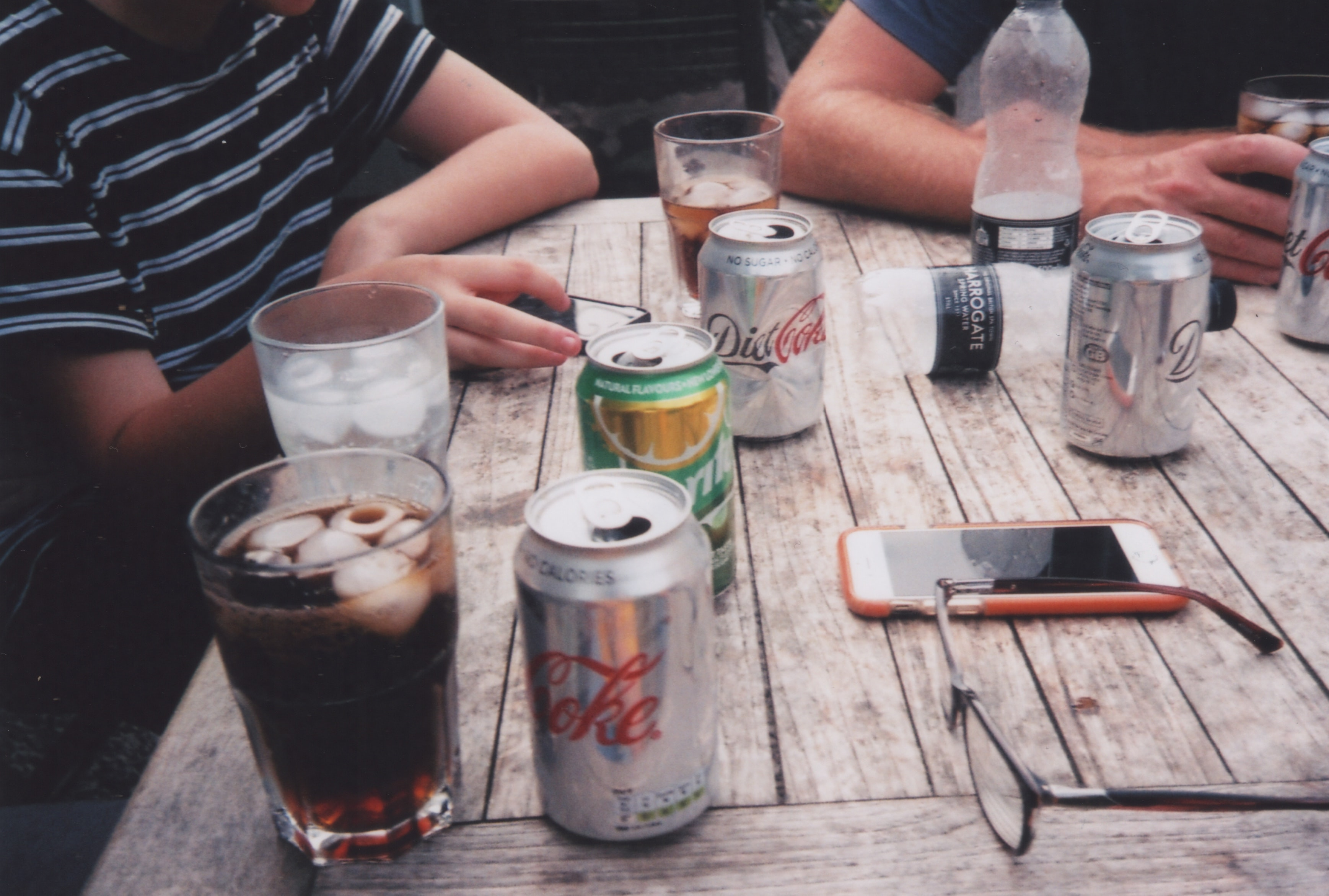 person sitting facing table with Coca-cola can
