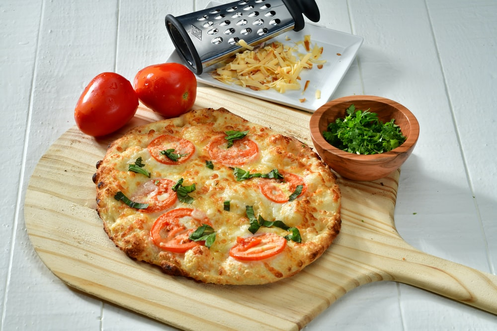 cooked pizza on brown wooden pizza board