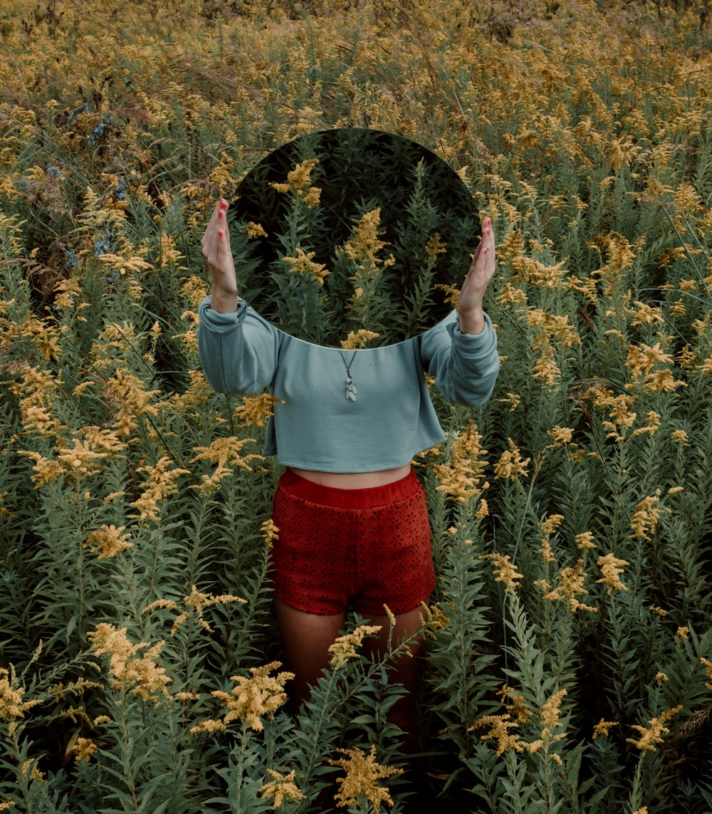 standing woman surrounded by yellow flower field during daytime