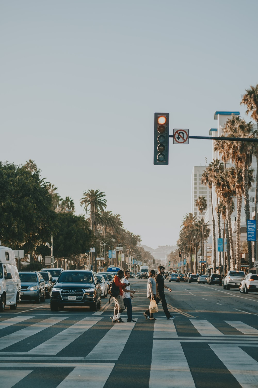 four person walking across the street under traffic light
