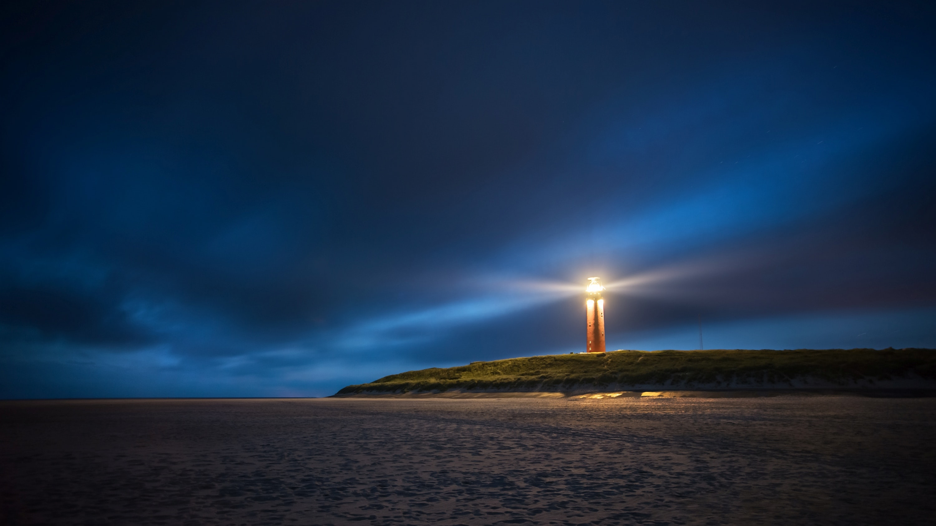 lighthouse under cloudy sky during nighttime
