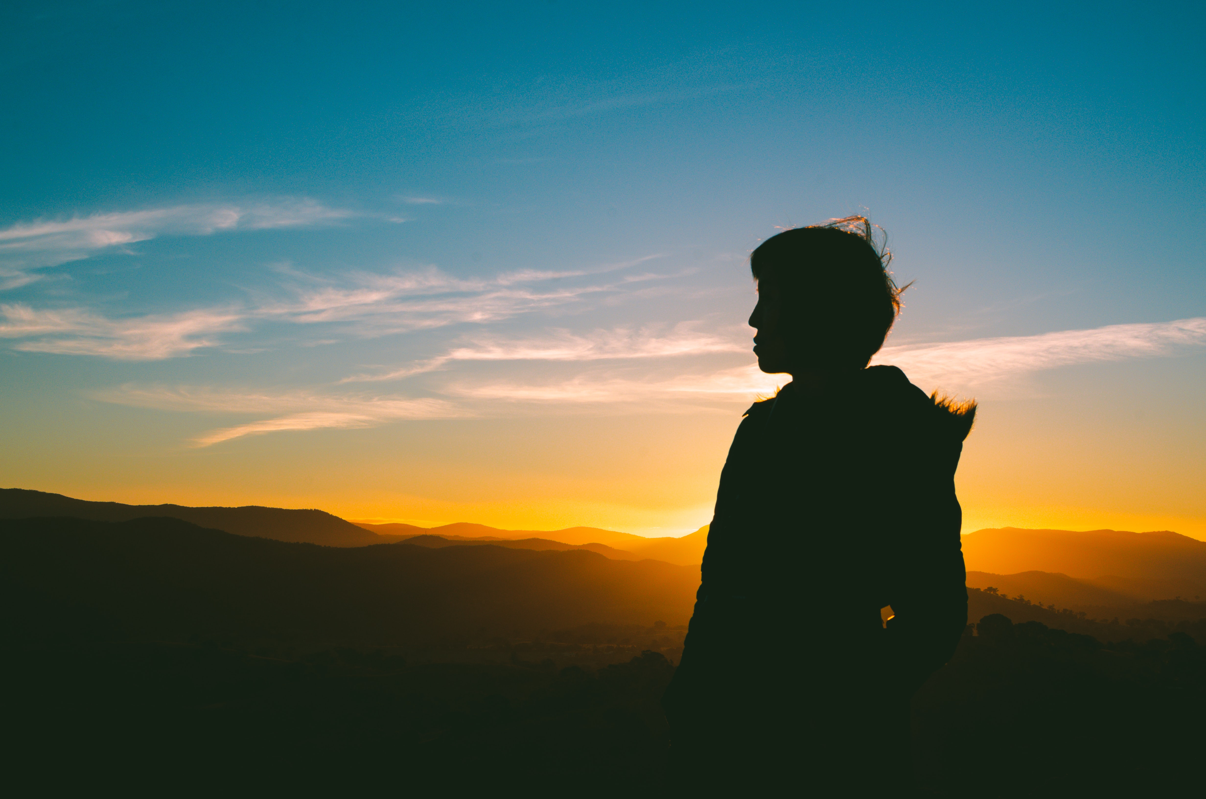 silhouette of person under blue sky