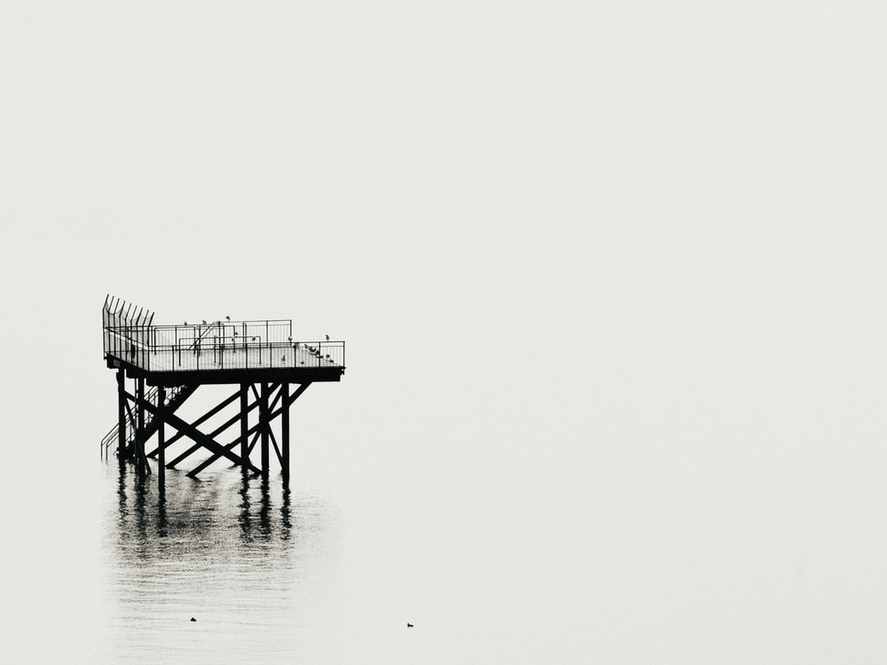 grayscale photography of tower above calm body of water