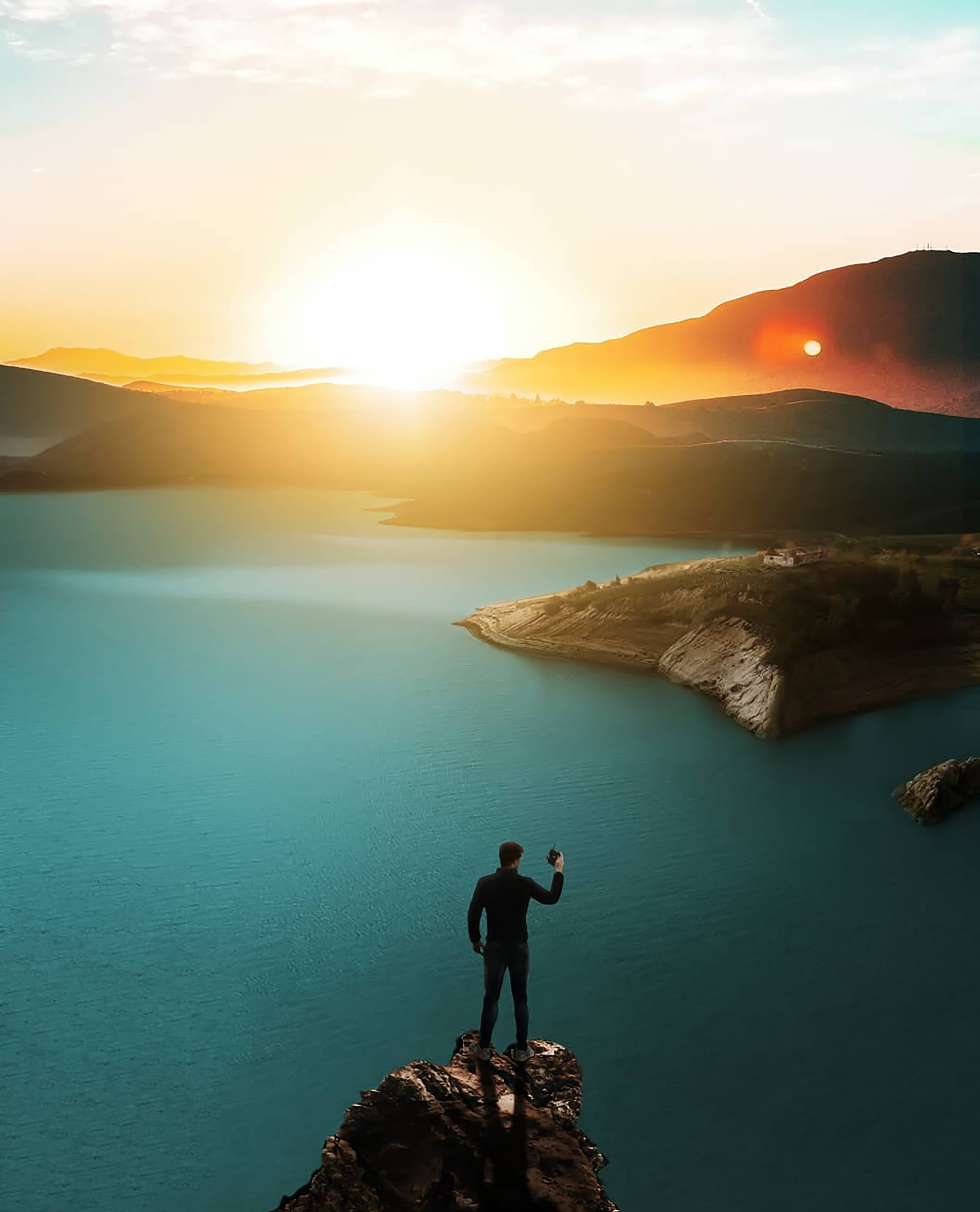 man standing on top of cliff above body of water during golden hour