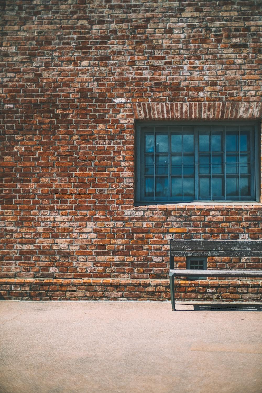gray bench beside brown brick wall