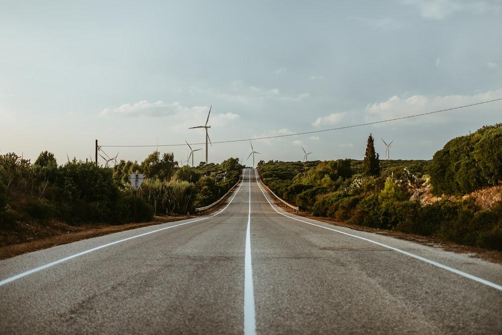 gray concrete road near windmills