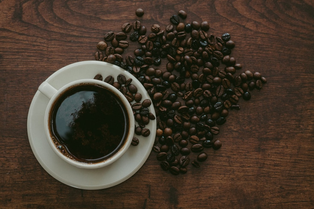 cup of coffee surrounded by beans