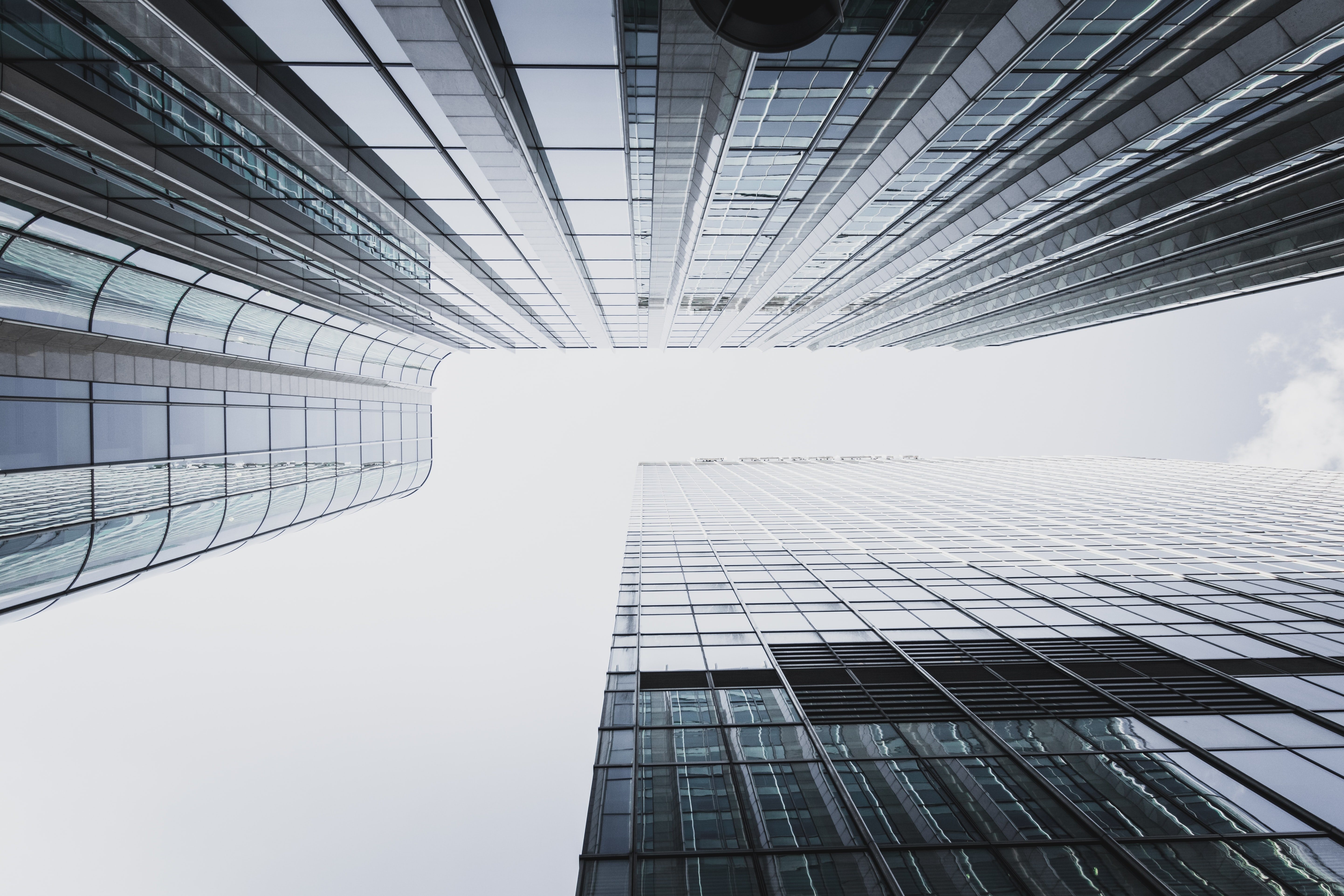 low-angle photography of two high rise curtain wall buildings under white clouds at daytime