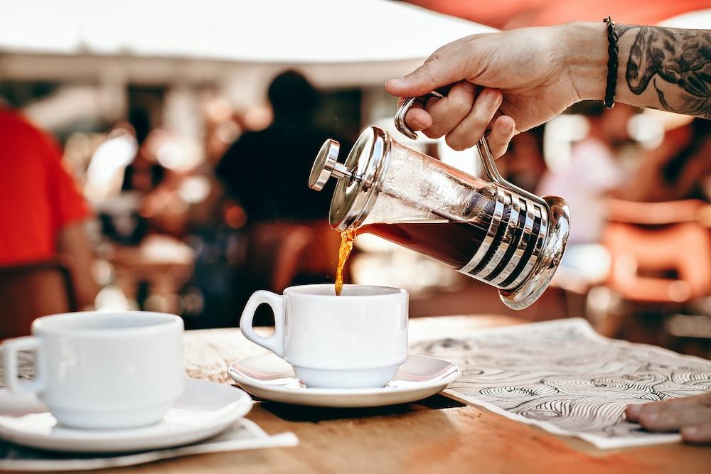 person pouring tea on white teacup