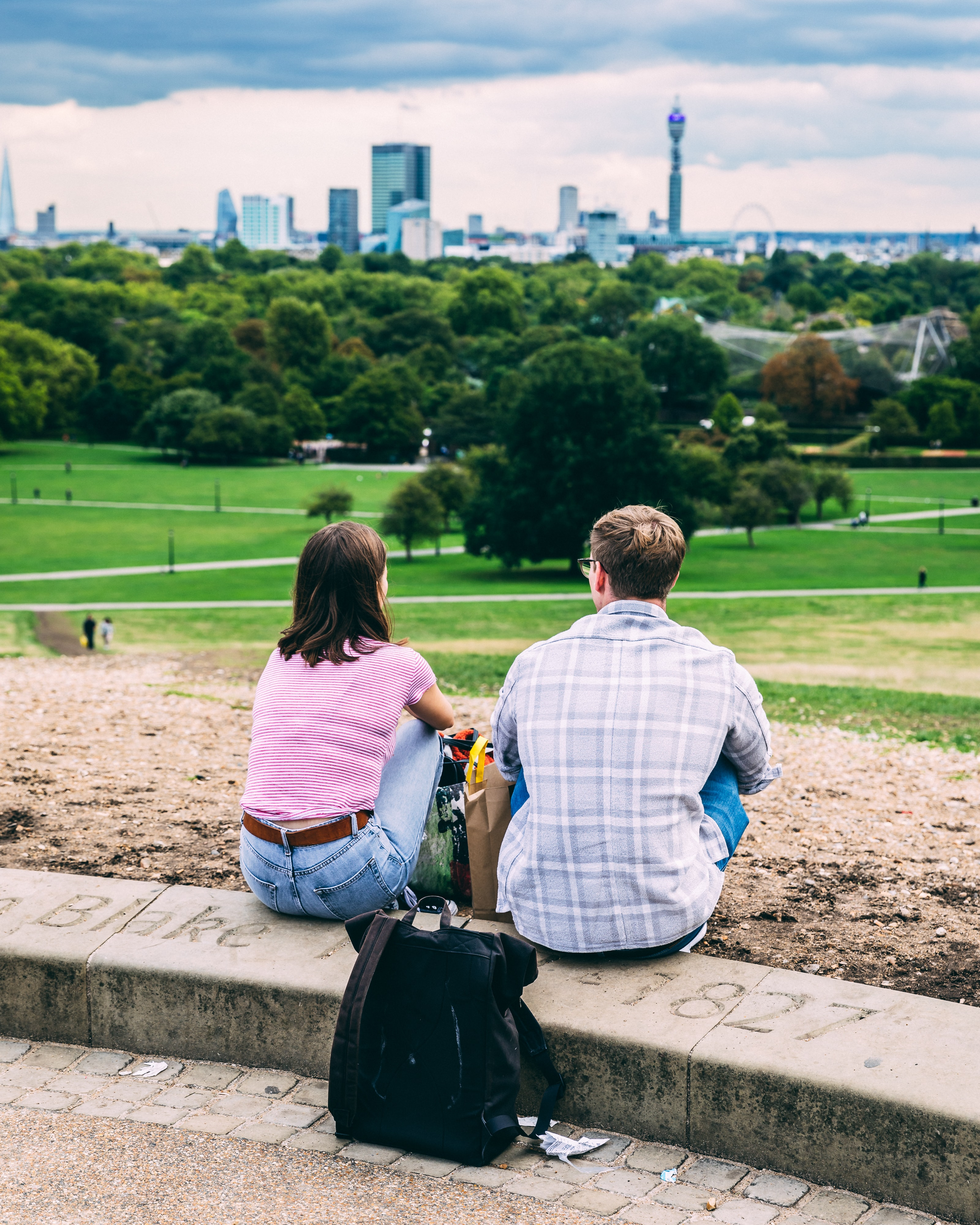 man and woman sitting under cloudy sky during daytime