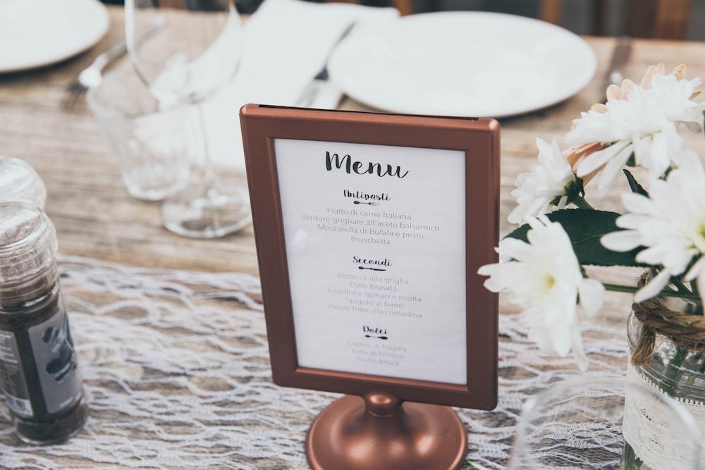 Menu-printed board with brown frame on table