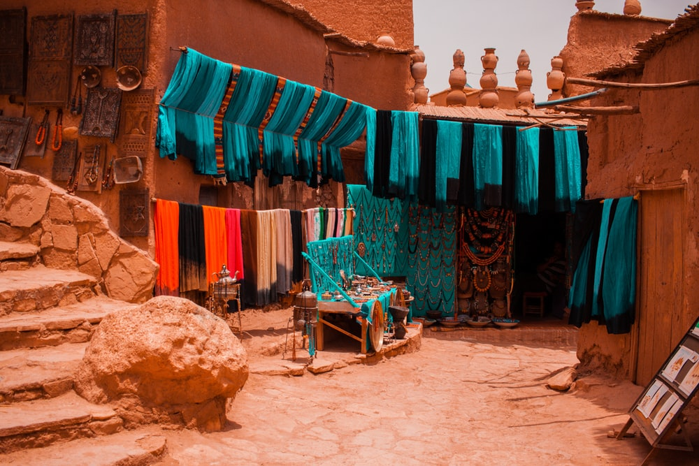 assorted-color textiles hanged beside concrete buildings
